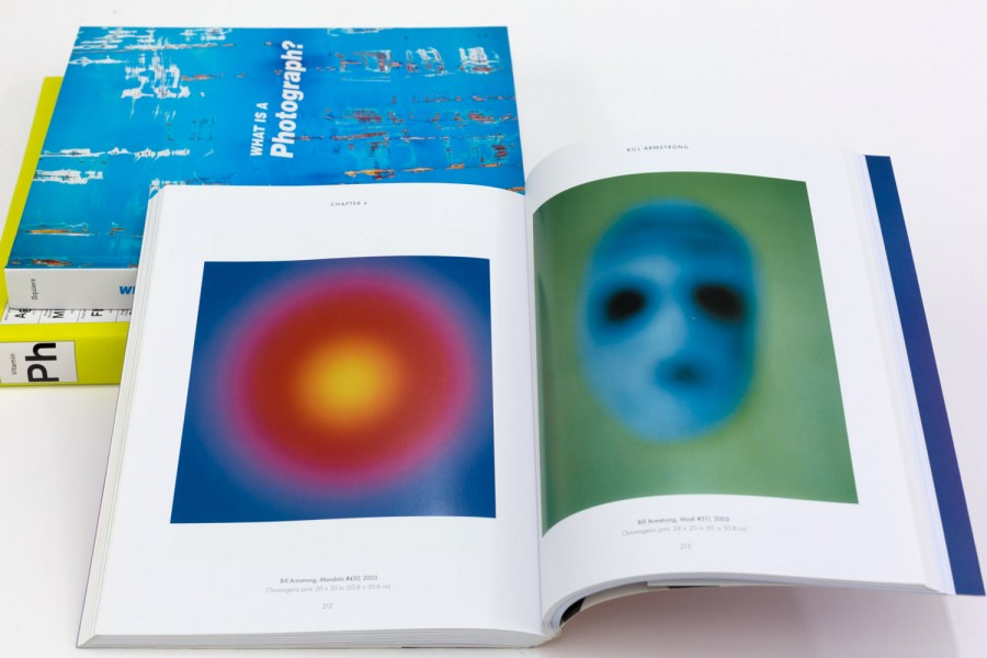 Two closed book and one open spread showing colorful digital prints.