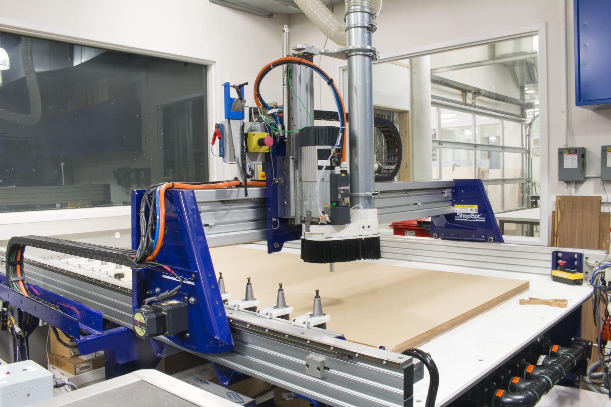 A view of the Shopbot CNC milling machine preparing to carve a sheet of acryllic.