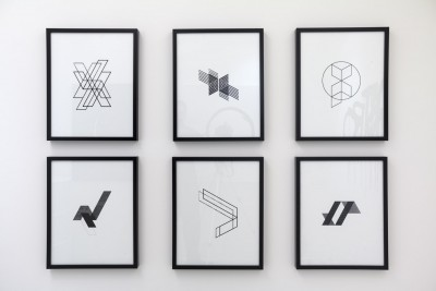 Six framed drawings hang on a white wall. The drawings are each framed with a solid black frame. The drawings each feature different geometrical shapes drawn in black on a white background.