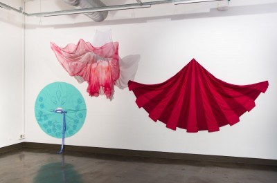 Three colorful fabric artworks by BFA Fine Arts student Menoara Mazid hanging on a white gallery wall.