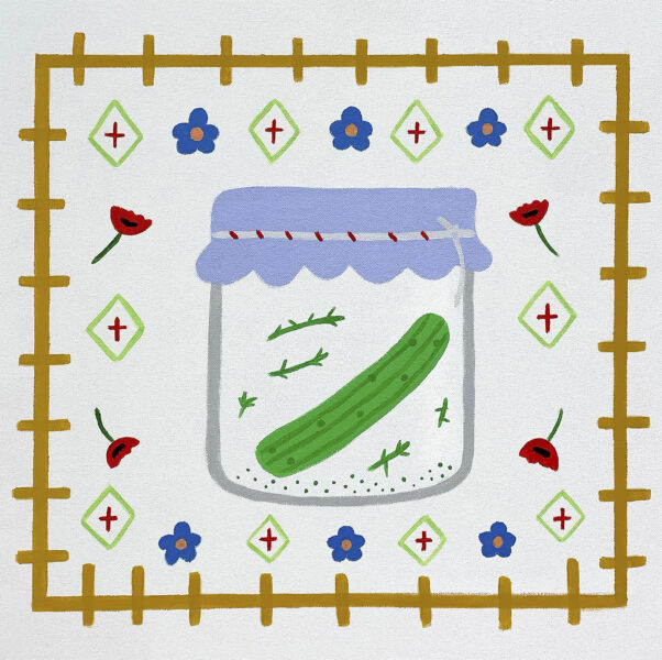 One green fermented pickle in a jar. Surrounding is poppy flowers, textile print, and blue flowers.