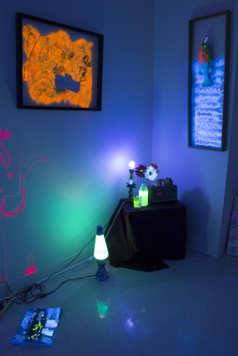Artwork installation by Nicasio Fernandez. The installation features a dark room that is lit up by neon lights in different colors. The room features miscellaneous objects on the floor and some hanging on the wall.