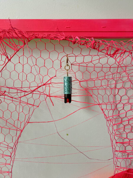 Stretcher bars with stretched chicken wire and thread stapled. Spray painted pink, mace keychain attached mid center and a high heeled patent leather boot attached on the right bottom side
