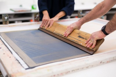 A large squeegee being pulled across a large silkscreen frame. An image of landscape can be seen on the frame.