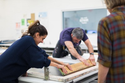 An instructor helps a student pull a large squeegee across a silkscreen frame.