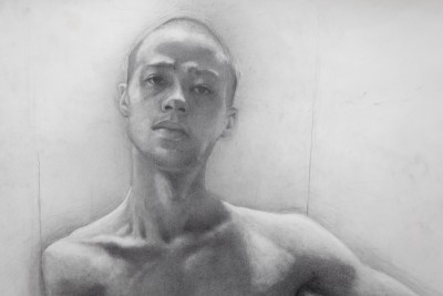 A drawing of a male model from the BFA Fine Arts drawing class. The drawing features the model from the shoulders up. The drawing of the model is facing forward with the gaze staring off to the side.