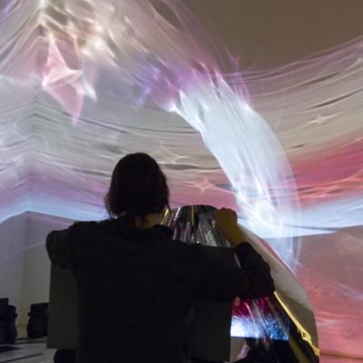 "Santa Dreimane: Body of Light(Anamorphism)"". 2013. Performative/Installation,video, projector, speakers, reflective plastics. Dimensions variable"