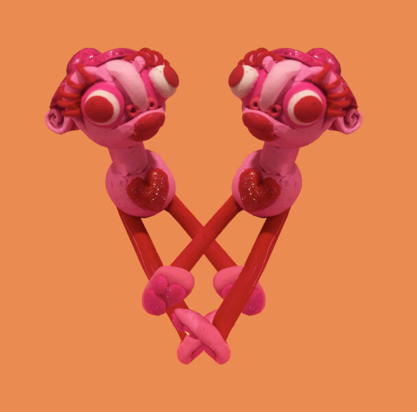 Orange back ground with two pinks clay figures with hats on