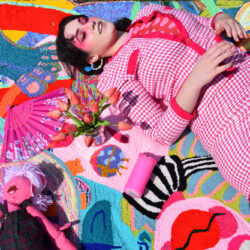 Colorful tufted rug with girl laying slanted on her back