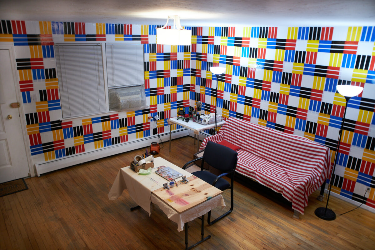 Red, blue, yellow, black and white duct tape which striped on the wall.