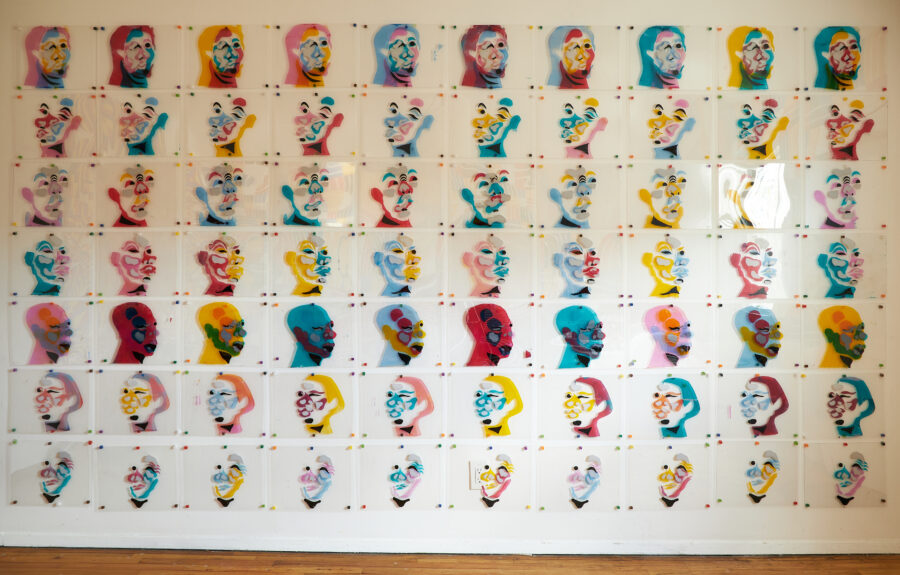 Silk screened the series of crushed faces on 70 sheets of plexiglass on the wall