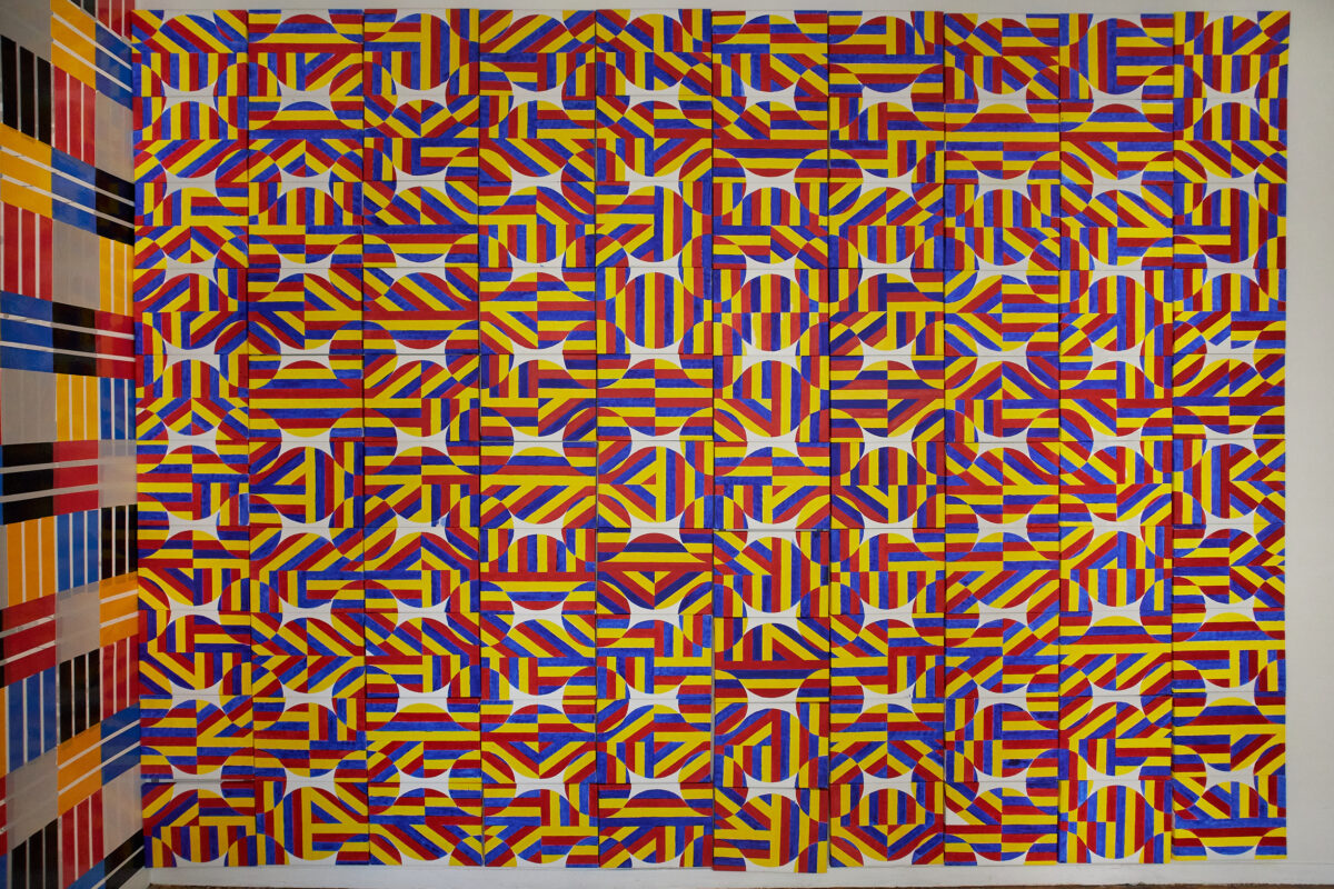 100 pieces of 12 x 9 inch canvas attached on the wall painted in colors of red, blue, and yellow stripes.