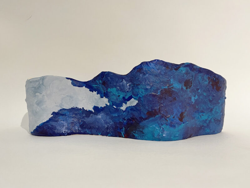 A mound of clay painted in blues and grays. From the artist: I think art shouldn't be limited by material, so I usually use more than one material in one work. This ceramic piece is about texture. The shape of this vase is waved, and I applied the wet clay onto the surface with palate knife to stimulate the sea wave. In addition, I painted the surface with acrylic to enhance the sense of texture.