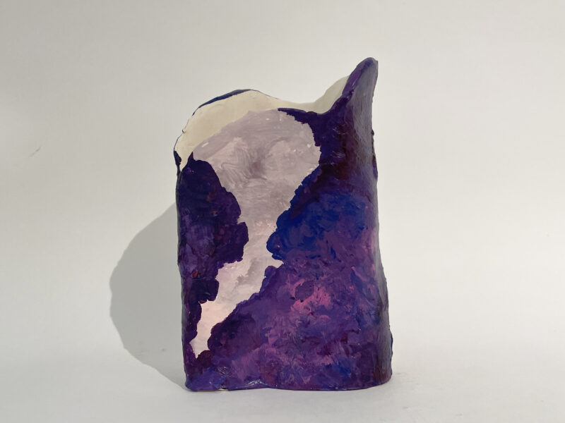 A mound of clay painted in purples and grays. From the artist: I think art shouldn't be limited by material, so I usually use more than one material in one work. This ceramic piece is about texture. The shape of this vase is waved, and I applied the wet clay onto the surface with palate knife to stimulate the sea wave. In addition, I painted the surface with acrylic to enhance the sense of texture.