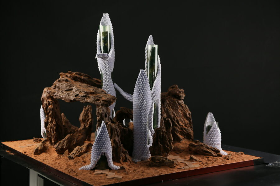 Artwork made of paper stone and sand. The forms look similar to buildings build in a rocky desert landscape. The sculpture is set on a platform against a black background.