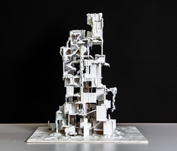 A sculpture made of wood and wax. The sculpture is covered in white wax and shows a construction that appears like a tall building with openings throughout.
