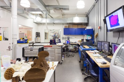 An interior view of the CNC Digital Sculpture lab. In the foreground are various works by students in Digital Sculpture. Also visible are two Epilog laser cutters, computer workstations, and a rapid prototyping machine.