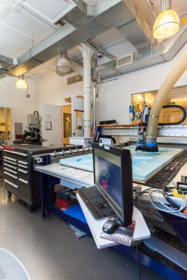 An interior view of the CNC Digital Sculpture lab. In the foreground is a large Shopbot CNC milling machine carving 3D shapes from a 4-foot by 8-foot sheet of blue polystyrene foam.