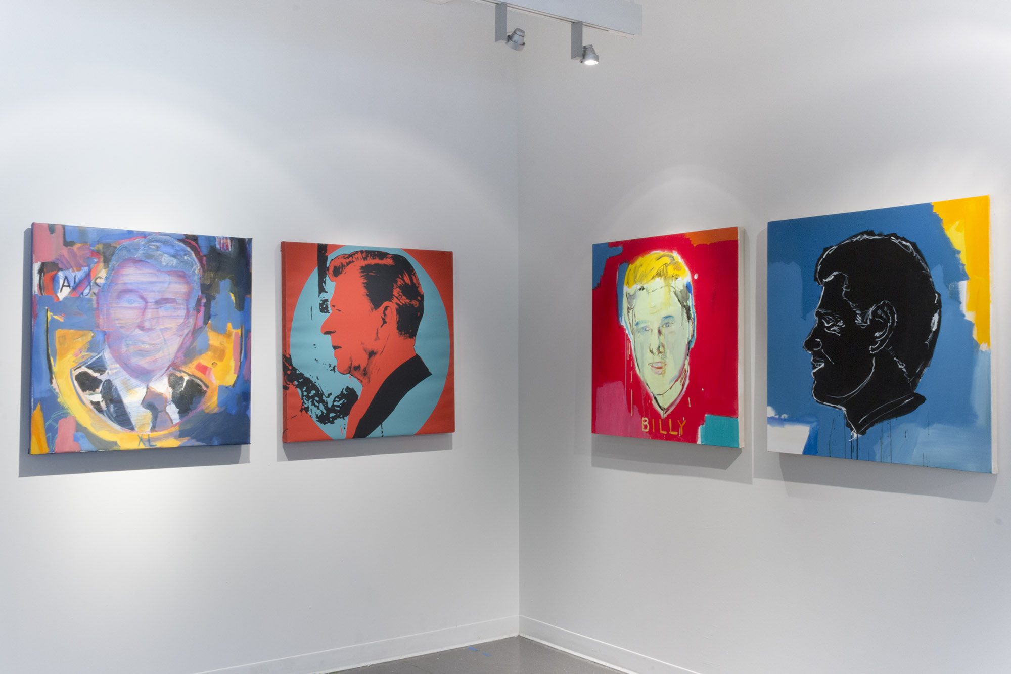 a photograph of a corner of a gallery with four paintings hanging on the wall. The paintings are square and feature a depiction of different US presidents on each painting with vibrant colors painted over them.