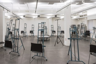 A photograph of a drawing classroom at the BFA Fine Arts building. The room is filled with chairs and easels formed in a circle around the room. In the center of the room is a platform for a model to stand on.