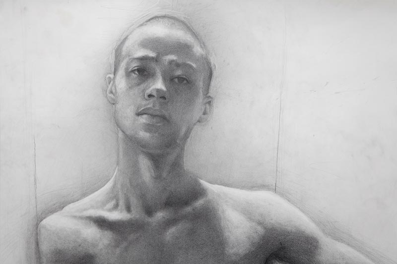 A graphite (pencil) selfportrait drawing by one Fine Art Student. It is rendered in a realistic style and the artist is looking straight at the viewer.