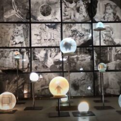 16 ink drawings in lightboxes in front of them are large snow globes 33lbs each on steel stands at various heights. The room is dark and the objects are dramatically lit.