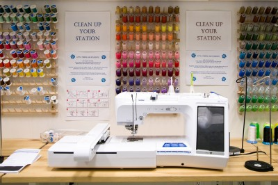 A photograph of a Brother digital embroidery machine in front of 3 racks of spools of embroidery thread in a wide array of colors.