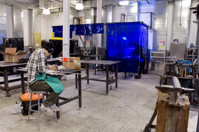 A student is working on the small metal table. Other student is welding in the MIG Welding staton covering with protection screen.
