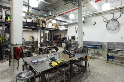 Safety equipments and sanding materials on the front table. Forming machines and Stationary sanding machine on the back. Student's metal works are on the wall.