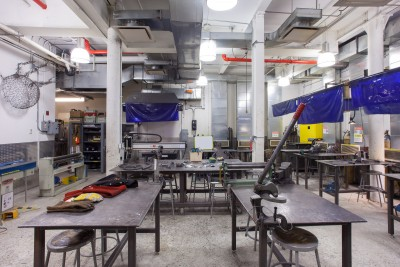 Welding Jacket, glove, helmet, safety equipment, hand roller and hand shear on the tables. Forming machines and Mig welding stations on sides. Safety Cabinet and CNC/Hand plasma cutter on the back.
