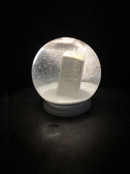 3D printed door looks like cartoon or distorted memory. The 3d printed door is sitting inside of a glass snowglobe.