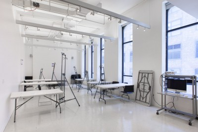 One of the painting classrooms in the BFA fine Arts building at the School of Visual Arts. The room is filled with white tables and metal painting easels. There are windows on the right side of the room.