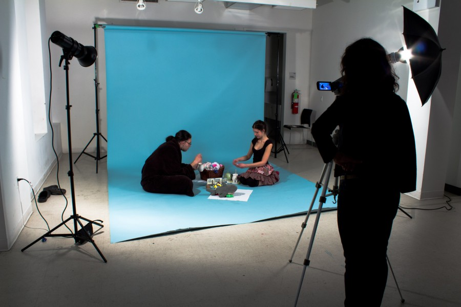 Students sit down on a blue seamless background. Lighting and a camera with tripod are part of the set.