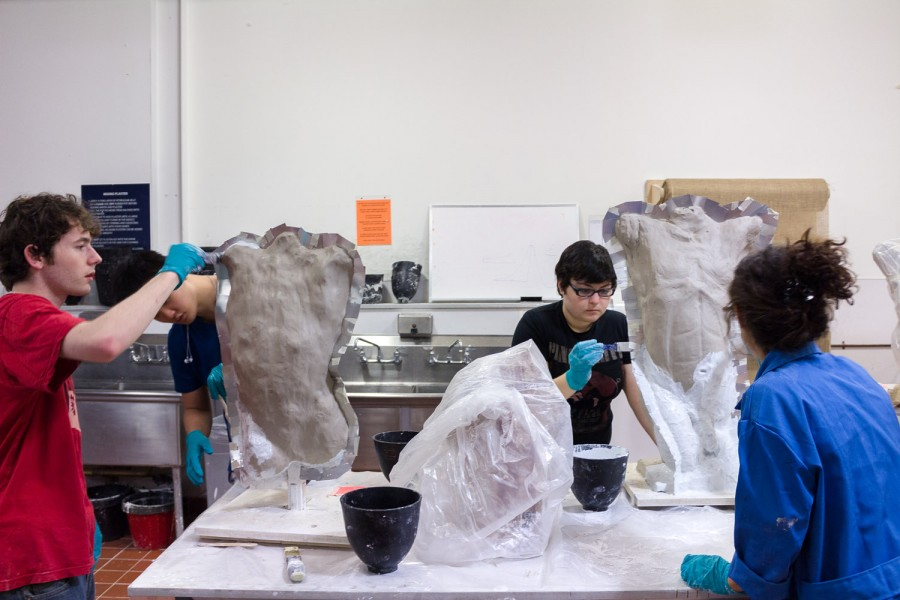 Three students working on mold making of human busts in the plaster workshop.